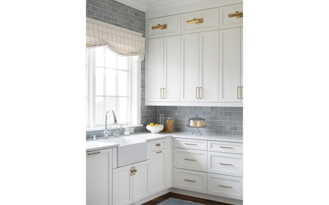 Kitchen with white cabinets and blue-gray tile backsplash