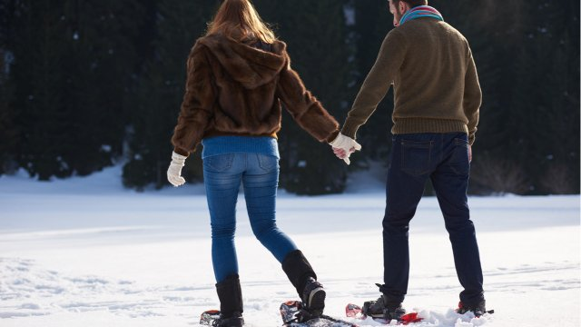 Couple holding hands and snowshoeing