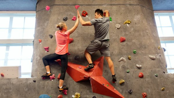 Couple high fiving on rock wall