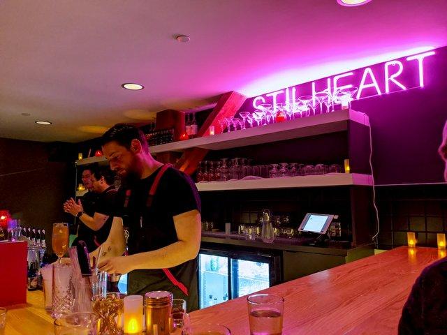 A bartender behind the Stilheart bar.