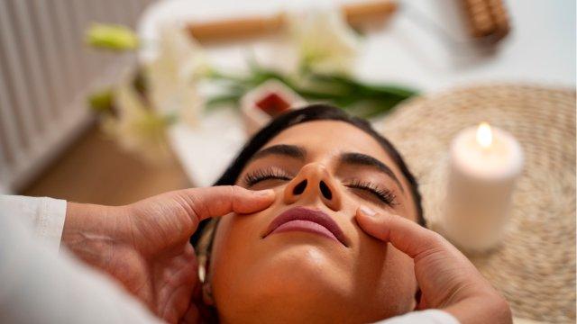 Closeup shot masseuse massaging sinuses of young woman