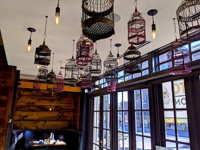 bird cages hung from the ceiling at Pajarito Edina