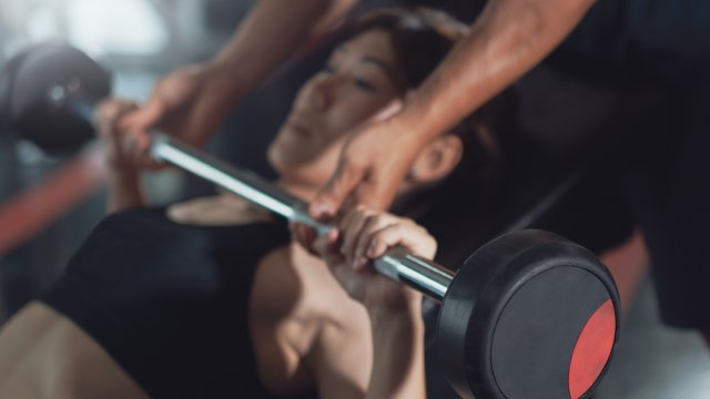 woman being spotted on barbell
