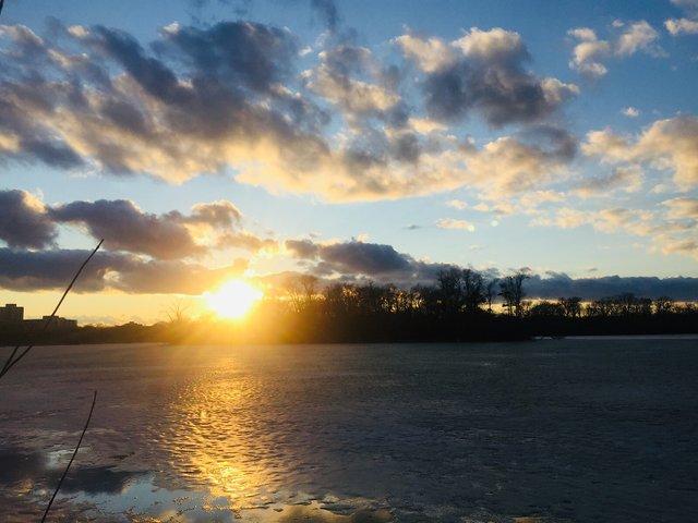 Winter sunset through clouds over Cedar Lake