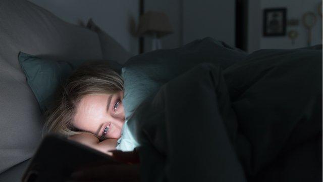 Woman lies awake on phone in bed at night