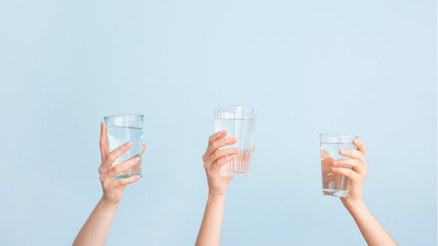 Three glasses of water held up by 3 hands