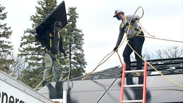 Man installing solar panels on home