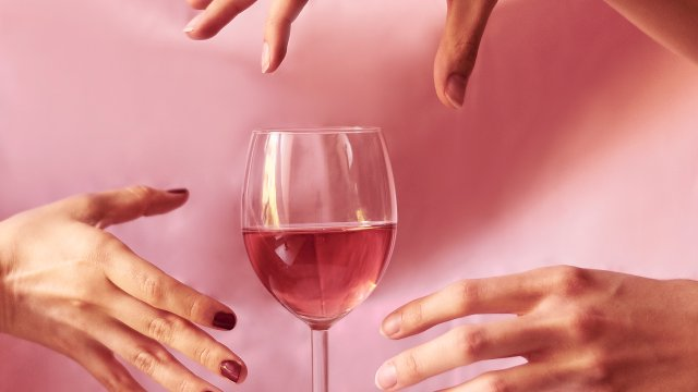 multiple women reaching out to grab a single wine glass