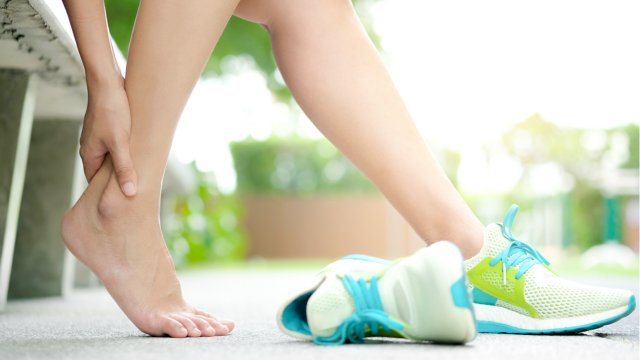 woman kicks off athletic shoes to relieve foot pain