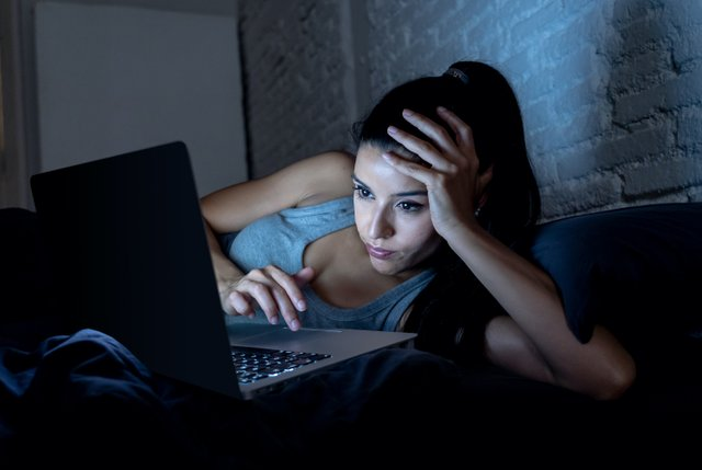 Girl laying down looking at computer (blue light from screen)