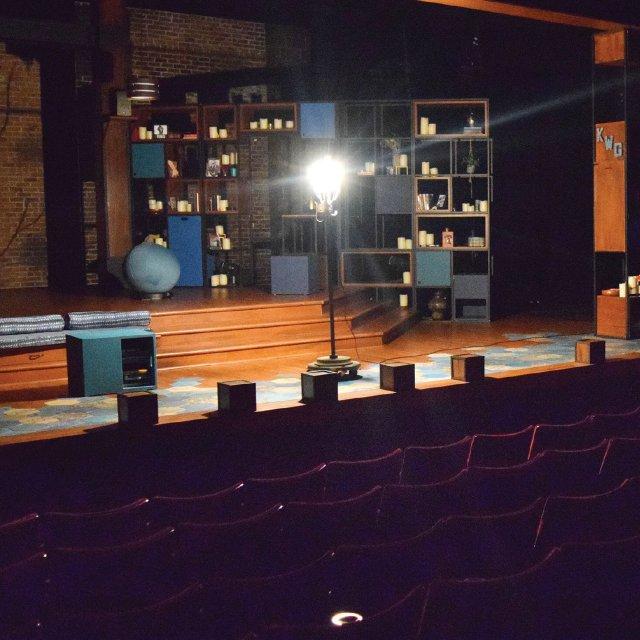 single light illuminates the empty stage