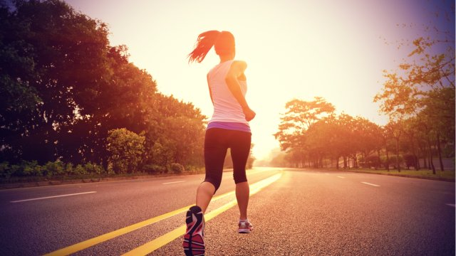 woman running on county road at sunset