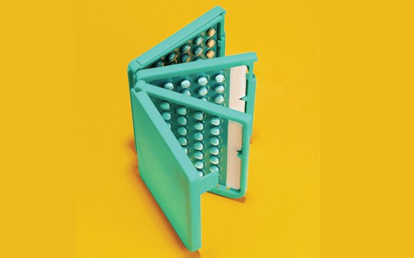 Green pack of birth control pills on a yellow background