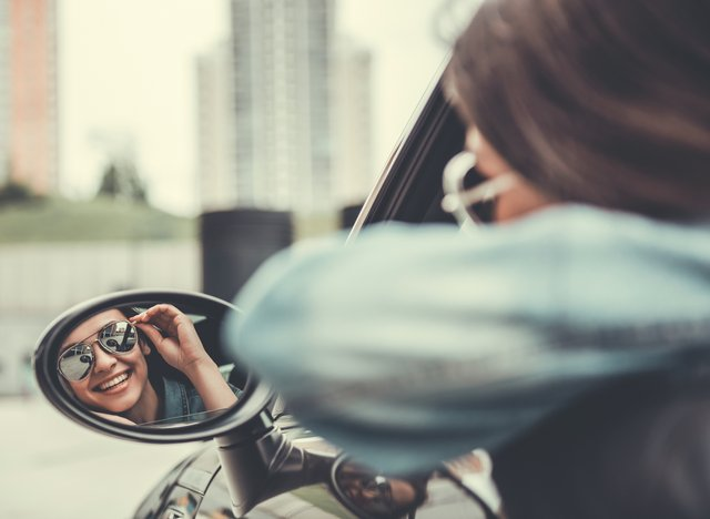 Girl Smiling in Car Mirror – Cosmetic Dentistry