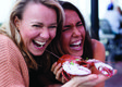 Women holding lobsters and smiling