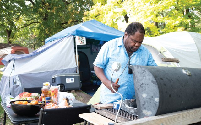Dre cooking in the homeless camp