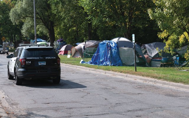 police car driving past homeless camp