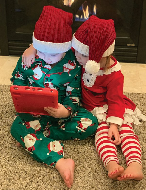 Kids in Santa hats looking at tablet