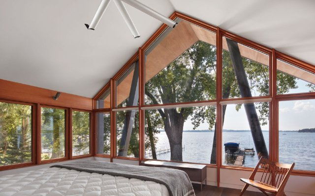 Loft bedroom with wall of window looking out on lake