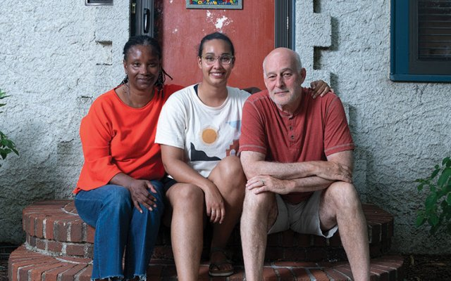 Mom dad and daughter sitting on front steps of their house