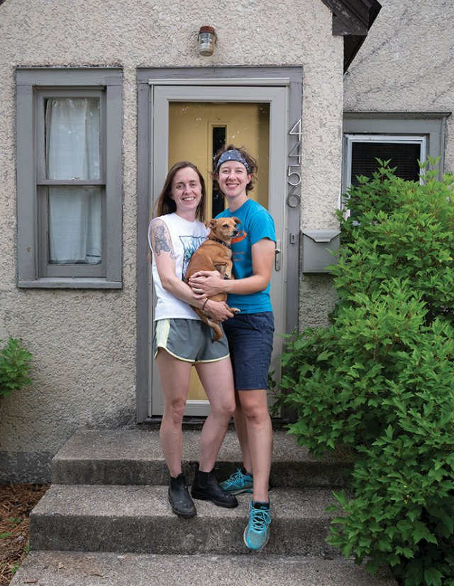Two women and their dog standing on the front steps of their house
