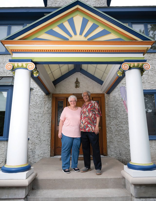 Older couple standing on the front steps of their house