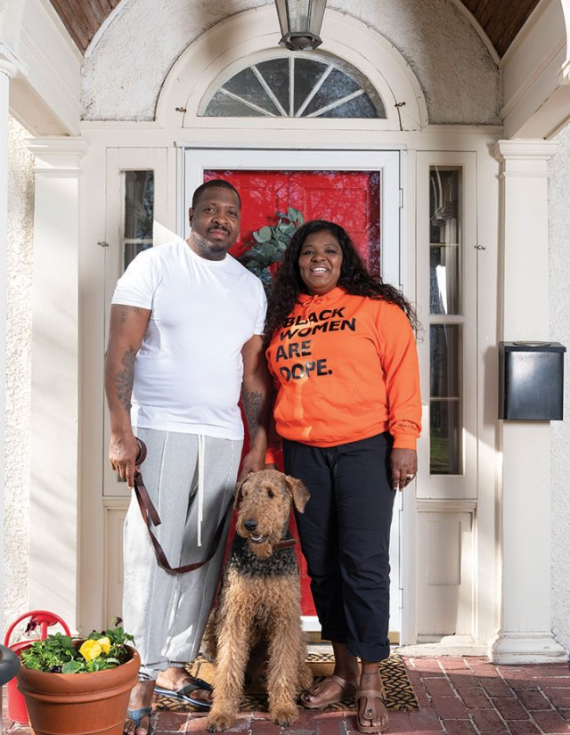 couple standing in front of their front door with their dog