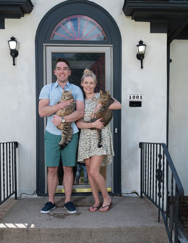 Young couple standing on their front steps with their two cats