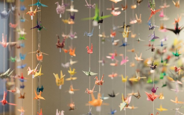 many many paper cranes hanging from strings
