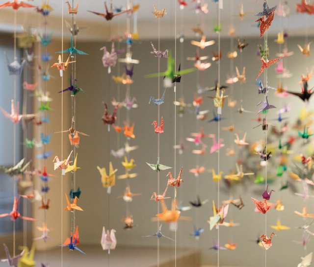 hundreds of paper cranes hanging from strings