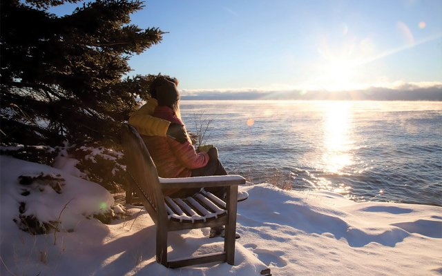 Couple sitting on lakeside bench in winter