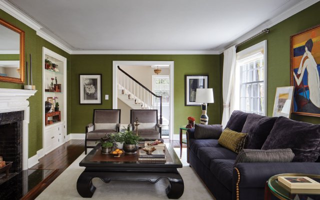 living room with green walls, white trim and hard wood floors