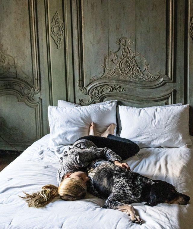 girl and dog sleeping on bed