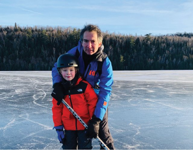 Father and son on frozen lake with hockey stick