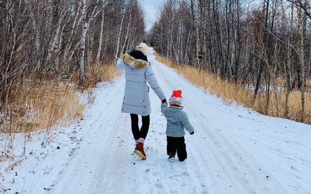 Mother and child walking down snowy road