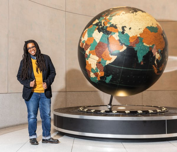 Woman standing next to a globe