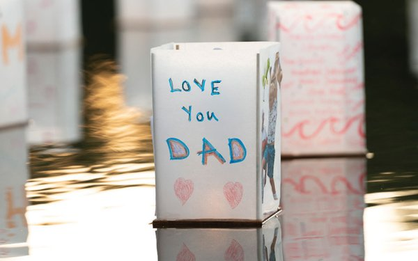 """floating candle with """"love you Dad"""" written on it."""