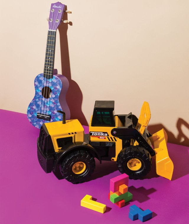 toy front loader and a ukulele with building blocks in the foreground