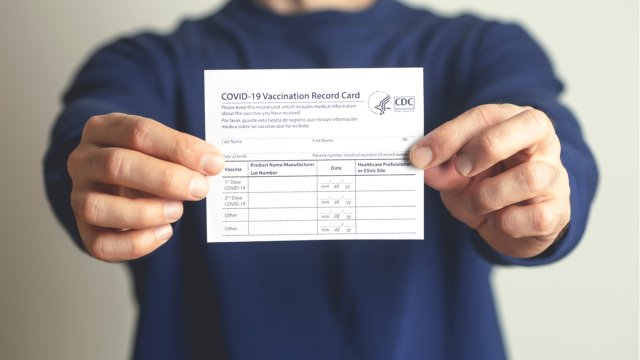 person holding up vaccination card