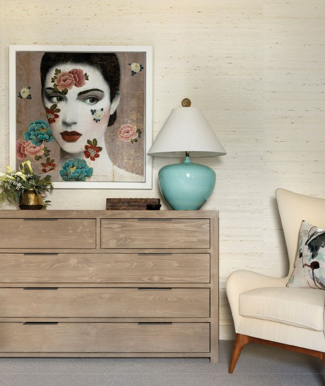 dresser with painting of a woman's face above