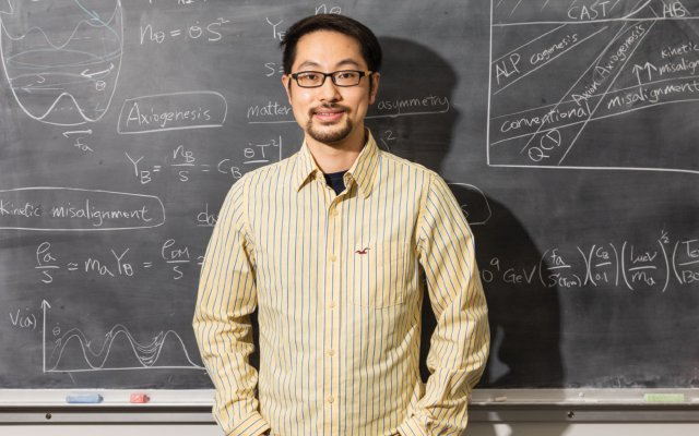 Raymond Co standing in front of a blackboard