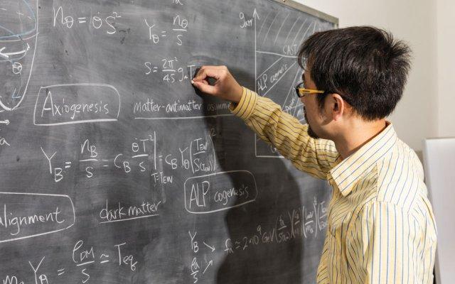 Raymond Co writing on a blackboard
