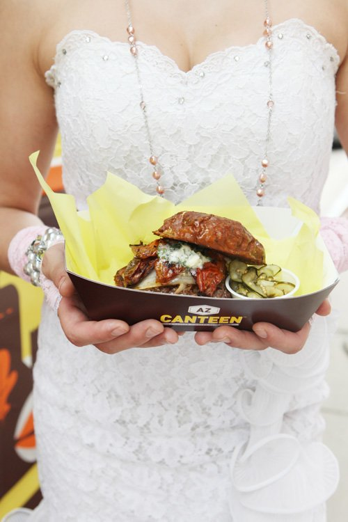 A bride holds food from AZ Canteen at her wedding | Photo by Katrina Hannemann