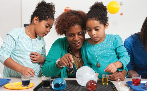 Woman and children performing science experiments