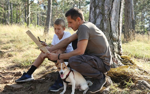 Man, boy, and dog in the wilderness