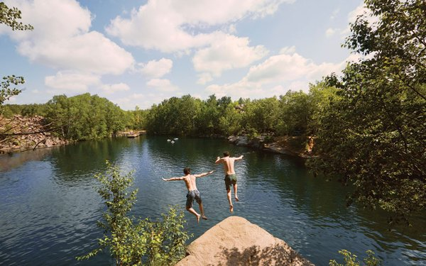 two kids jumping into a lake