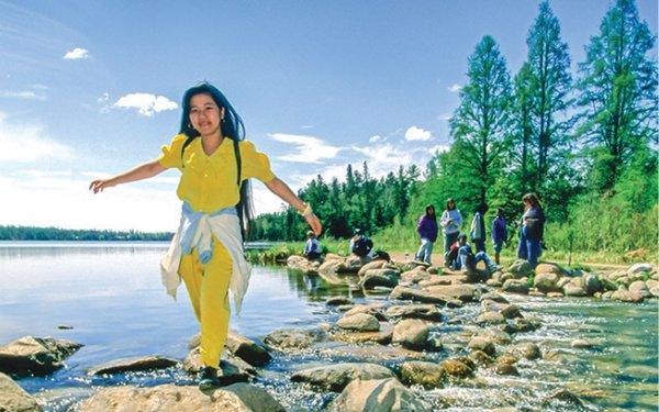 girl walking on some rocks by a lake