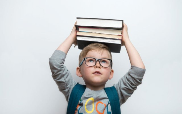 kid with book balancing on his head