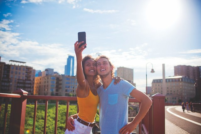 young man and woman take selfie on Stone Arch Bridge