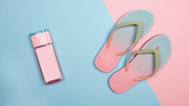flat lay of blue-pink sandals and pink sunscreen bottle